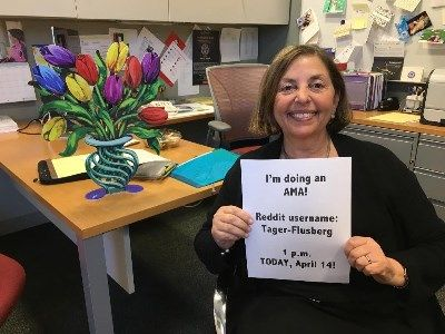 Image of Boston College Professor Helen Tager-Flusberg holding a piece of paper promoting here AMA on Reddit
