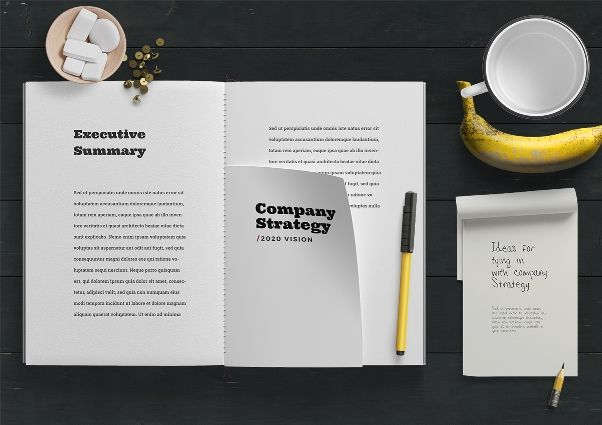 Image of an open notepad with 'Company Strategy' text; also cup and banana in picture
