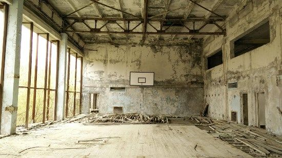 Picture of a ruined indoor basketball court in chernobyl