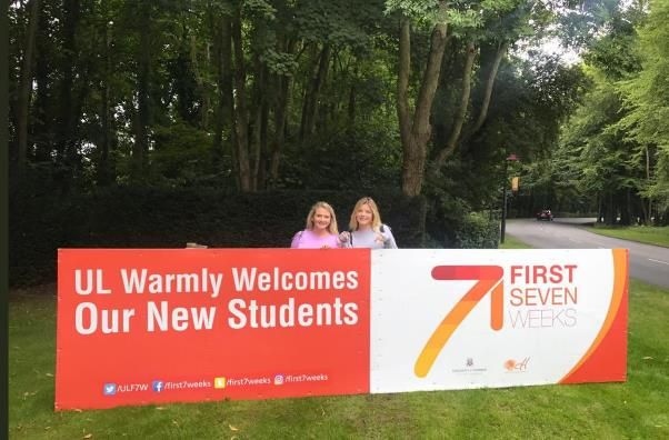 2 girls standing in front of a sign saying 'UL Warmly Welcomes Our New Students'