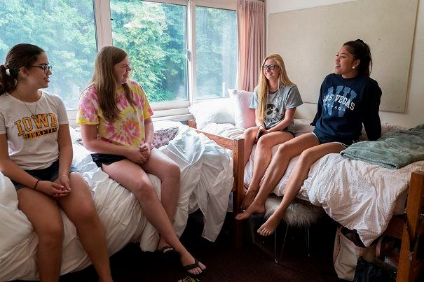 Four girls in shorts and t-shirts sitting on beds in a college dorm room